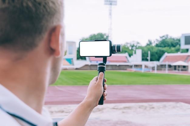 スタジアムのブロガーは、手動のカメラスタビライザーを備えたスマートフォンでビデオを撮影します。