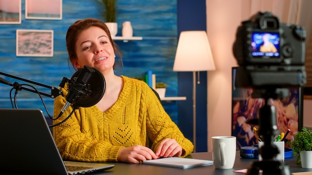 Blogger influencer recording video blog concept speaking looking at camera on tripod in home podcast studio