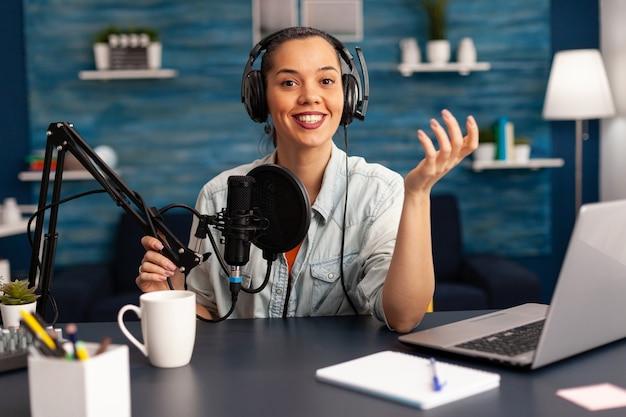 オンライントークショーのホームスタジオでプロのカメラを見ているブロガーインフルエンサーレコーディングビデオブログ。ソーシャルメディアコンテンツクリエーターが彼女のチャンネルのシリーズを作成し、オンライン放送をストリーミング