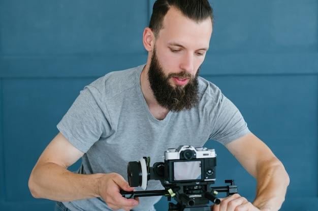 ブロガーのライフスタイルと作業プロセス。ビデオストリーミングを開始するためにカメラをセットアップするひげを生やしたヒップスターの男。ソーシャルネットワークのトレンドとインターネットビジネスの概念。