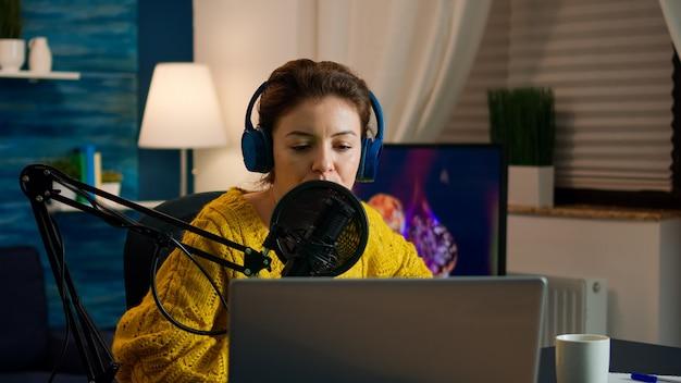블로거가 홈 스튜디오에서 새 팟캐스트를 녹음하는 추종자들과 이야기하기 시작하는 노트북을 엽니다. 온에어 온라인 제작 인터넷 방송 쇼 호스트 스트리밍 라이브 콘텐츠, 디지털 비디오 녹화 vlog