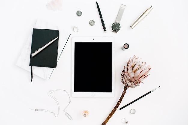 空白の画面タブレット、プロテアの花、ノート、時計、白い背景に女性のアクセサリーを備えたブロガーまたはフリーランサーのワークスペース。フラット レイアウト、トップ ビュー ミニマルな装飾が施されたホーム オフィス デスク。
