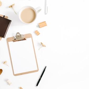 클립 보드, 커피 잔, 노트북 및 액세서리가있는 블로거 또는 프리랜서 작업 공간. 평면 배치, 상단보기 최소한의 갈색 스타일의 홈 오피스 데스크. 뷰티 블로그 개념.
