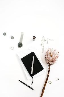白い背景にプロテアの花、ノート、フェミニンなアクセサリーを持つブロガーまたはフリーランサーのワークスペース。フラット レイアウト、トップ ビュー ミニマルな装飾が施されたホーム オフィス デスク。美容ブログのコンセプト。