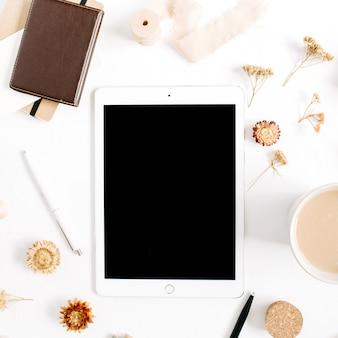 태블릿, 커피 머그잔, 노트북 및 액세서리 흰색 배경에 블로거 또는 프리랜서 작업 영역. 평면 배치, 상단보기 최소한의 갈색 스타일의 홈 오피스 데스크. 뷰티 블로그 개념.