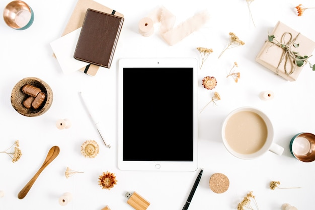 태블릿, 커피 머그잔, 노트북, 과자 및 액세서리가있는 블로거 또는 프리랜서 작업 공간. 평면 배치, 상단보기 최소한의 갈색 스타일의 홈 오피스 데스크. 뷰티 블로그 개념.