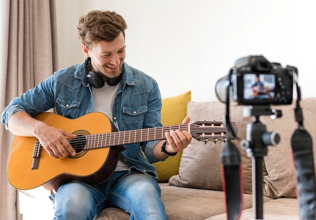 Blogger playing guitar on camera