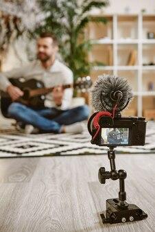 Блогер играет на гитаре и записывает новое видео для своих подписчиков. youtube. музыкальный блог