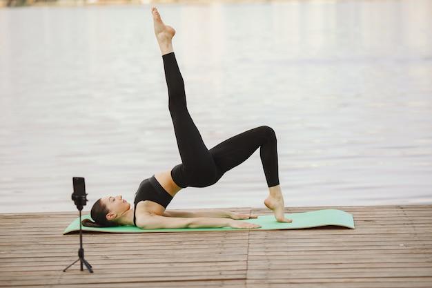 Blogger che pratica yoga avanzato sull'acqua