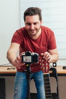 Blogger готовит камеру для записи урока игры на гитаре в своей домашней студии