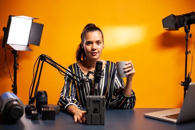 홈 스튜디오에서 팟캐스트를 위해 배터리 리뷰를 녹음하는 blogger