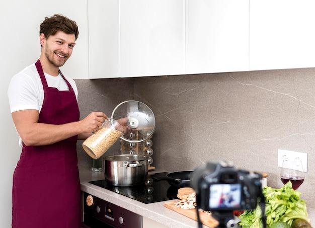 Blogger che registra cucinando video a casa