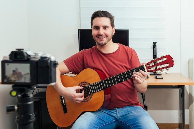 Блогер записывает урок игры на гитаре в своей домашней студии.