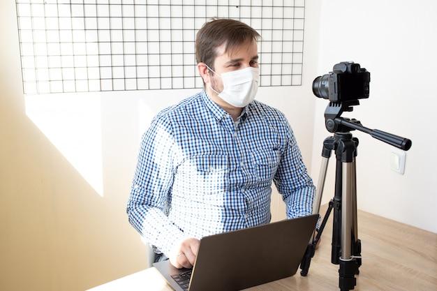 コロナウイルスの検疫、コロナウイルス、病気、感染症、検疫、医療用マスクについて家にいる間、自宅でビデオを記録するブロガー