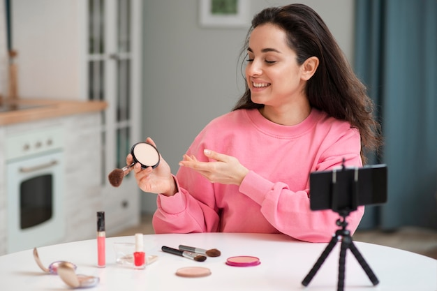 Blogger recording video with make-up accessories
