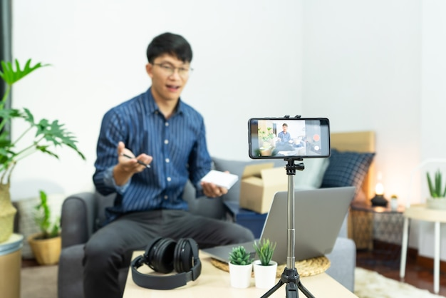 Blogger recording vlog video on camera review of product at home office