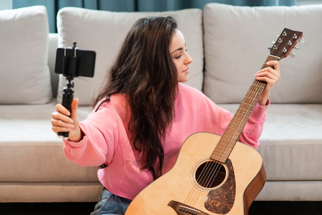 Blogger recording with smartphone her guitar
