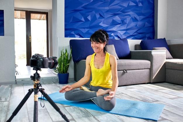 집에서 요가 하 고 스포츠에 슬림 몸 모양으로 블로거 수석 여자. 피트니스 블로그, 비디오 튜토리얼, 카메라로 비디오 요가 레슨을 녹화하는 온라인 교육.