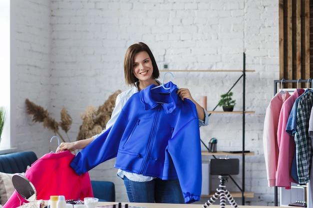 Блогер показывает одежду на камеру, записывает видео-урок для своего модного блога.