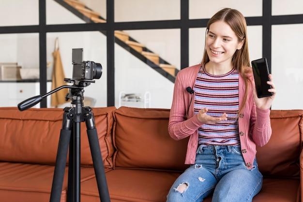 Блогер сидит на диване и показывает свой смартфон