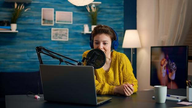 헤드폰을 사용하여 라이브 팟캐스트에서 팔로워와 이야기하는 블로거. 크리에이티브 온라인 쇼 온에어 프로덕션 인터넷 방송 호스트 스트리밍 라이브 콘텐츠, 디지털 소셜 미디어 커뮤니케이션 녹음