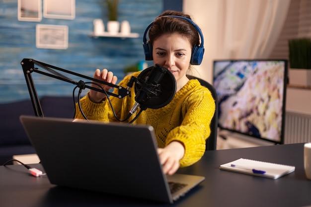 헤드폰을 사용하여 라이브 팟캐스트에서 팔로워와 이야기하는 블로거. 창의적인 온라인 쇼 온에어 프로덕션 인터넷 방송은 라이브 콘텐츠를 스트리밍하고 디지털 소셜 미디어 커뮤니케이션을 녹음합니다. 프리미엄 사진