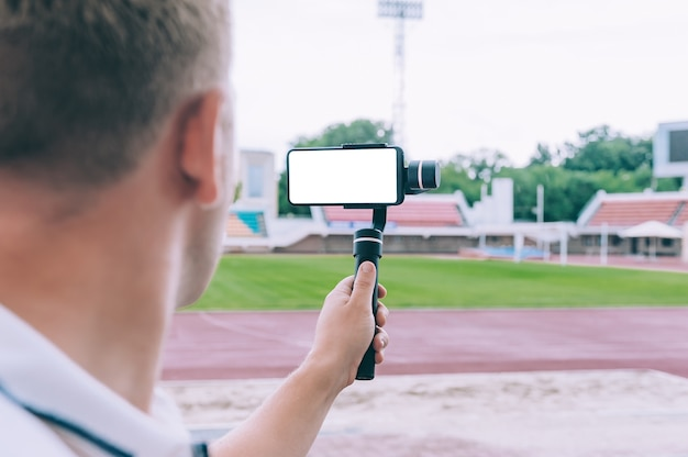 Blogger in the stadium shoots video on a smartphone with a manual camera stabilizer.
