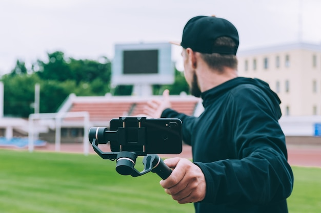 Blogger in the stadium shoots video on a smartphone