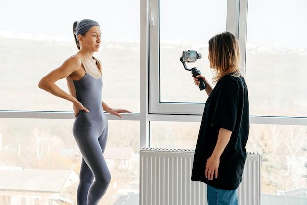 Блогер транслирует и берет интервью у тренера по йоге в тренажерном зале с помощью смартфона и gimble