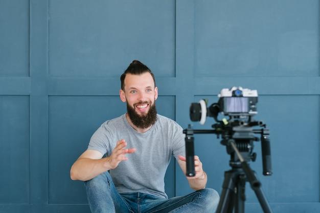 Blogger в прямом эфире. бородатый хипстерский мужчина общается с подписчиками через камеру. новые современные занятия и способы заработка в интернете.