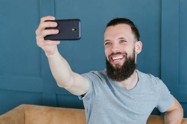 Blogger транслирует прямые трансляции с мобильного телефона. бородатый хипстерский мужчина общается с подписчиками через камеру. новые современные занятия и способы заработка в интернете.