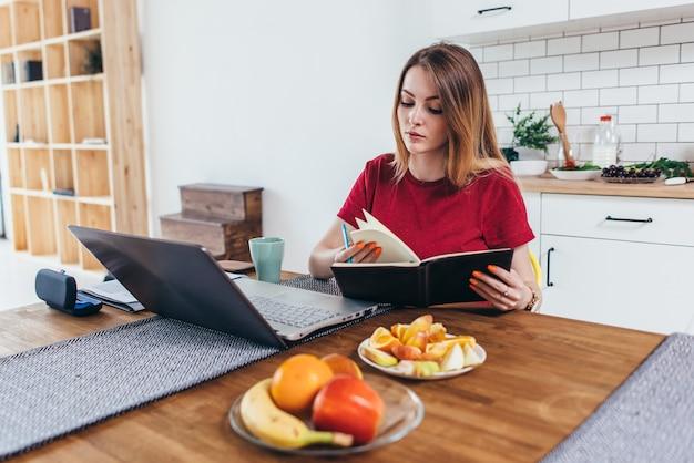 ブロガー。オンラインで学ぶ学生。テーブルに座って、ノートにメモを取る女性。