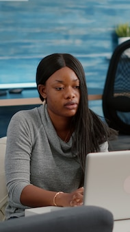 Blogger student with dark skin working from home browsing communication information