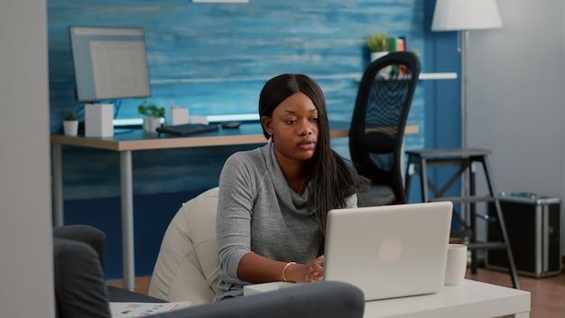 Студент blogger с темной кожей, работающий из дома, просматривает информацию для общения