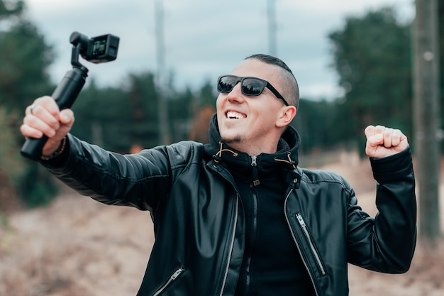 Blogger in sunglasses making selfie or streaming video at the pine forest using action camera with gimbal camera stabilizer.