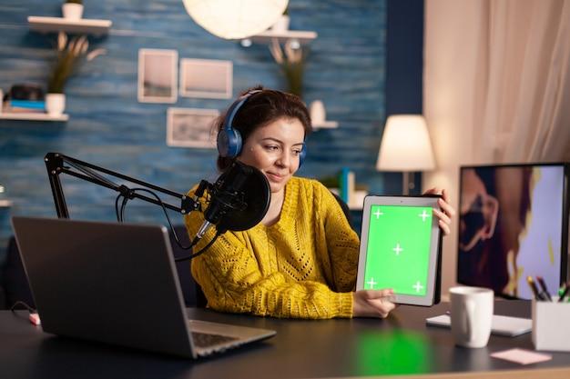 엔터테인먼트 팟 캐스트 방송 중 녹색 화면이있는 메모장을 들고 마이크에 말하는 블로거.