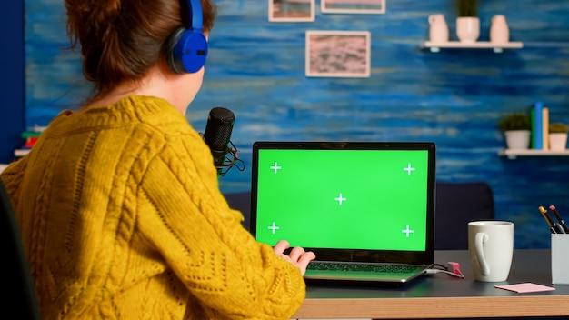 청중을위한 새로운 팟 캐스트 시리즈를 녹화하는 녹색 화면 디스플레이로 노트북에 입력하는 blogger