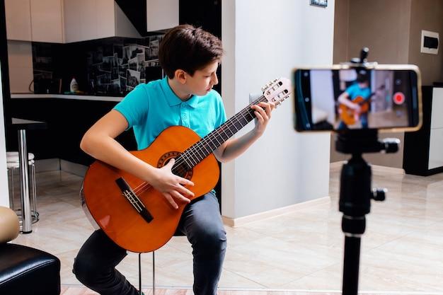 ブロガーはギターを弾きながら自宅で彼のvlogをビデオテープに録画します。