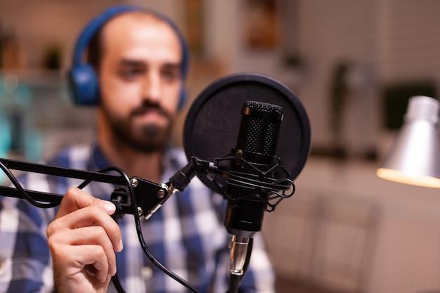 Blogger che indossa le cuffie e parla dello stile di vita durante il podcast show online creativo produzione in onda host di trasmissione su internet streaming di contenuti live registrazione comunicazione sui social media digitali