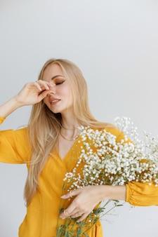 明るい化粧と白い花を持つブロガーは彼の手で彼の顔を覆います。ファッショナブルなムード