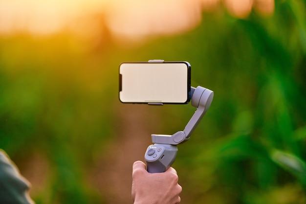 흰색 빈 화면 모형이 있는 전자 수동 전화 안정기 짐벌이 있는 블로거는 셀카를 찍고 야외에서 비디오 블로그를 촬영합니다.