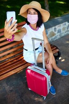 Блогер женщина в защитной маске, в парке на улице с чемоданом, возьми селфи
