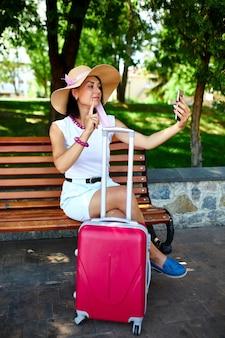 Женщина-блогер в соломенной шляпе со снятой маской держит на голове, в парке на открытом воздухе с чемоданом, делает селфи, жизнь во время пандемии коронавируса, открывает воздушное путешествие, концепция путешествия.