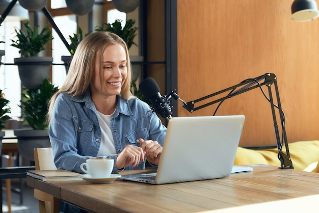 Blogger woman talking with followers online by laptop