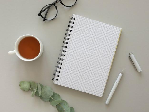 ブロガー職場フラットレイアウトモックアップ。ヒップスターのメガネと開いたノートブック、空の紙、お茶、ユーカリ。
