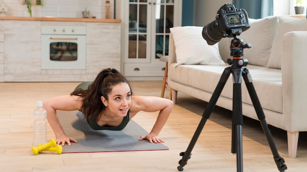 Blogger on yoga mat recording herself with camera