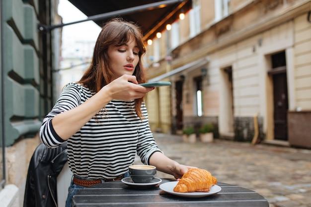 携帯電話でコーヒーとクロワッサンの写真を撮るブロガーの若い女性