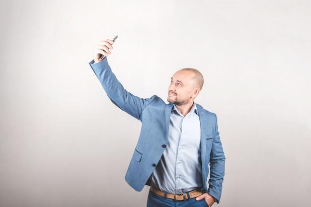 Стильный мужчина в деловой куртке принимает селфи. молодой человек смотрит в камеру смартфона. blogger на светлой поверхности