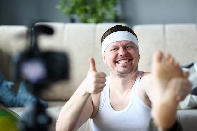 Веселый blogger делать упражнения и держать палец вверх