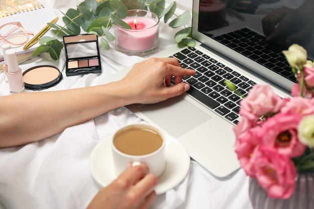 女の子はラップトップで働いています。 bloggerワークスペース。フリーランサーのコンセプト